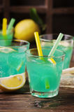 Green cocktail with lemon and ice on the wooden table Royalty Free Stock Photo
