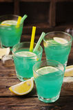 Green cocktail with lemon and ice on the wooden table Stock Photo