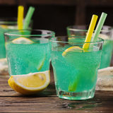 Green cocktail with lemon and ice on the wooden table Royalty Free Stock Images