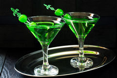 Green cocktail with maraschino cherry in a martini glasses Royalty Free Stock Photo