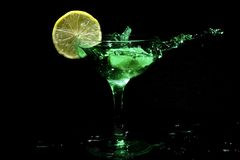 Green cocktail splashing in a glass. With citron Stock Photo