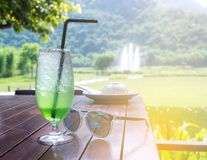 Green cocktail and sunglasses resting on a wooden table with a natural background stock photography
