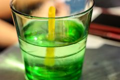 A green cocktail with a yellow strawberry in a transparent glass stock photo