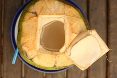 Green coconut with choped off top and straw. Close up photo Royalty Free Stock Photography