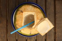 Green coconut with choped off top and straw. Close up photo Royalty Free Stock Images