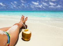Green coconut and legs of a young girl Royalty Free Stock Photo