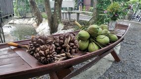 Green Coconut and Nipah palm in wooden boat Stock Photo