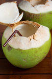 Green coconut water drink. On wooden table Stock Photography