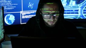 Green code characters reflect on face hacker in dark office room, cyber security center filled with display screens. Working on computer, IT professional stock footage