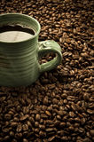 Green Coffee. Cup resting in a pile of coffee beans Stock Images