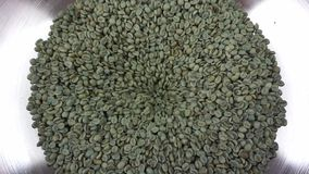 Green coffee beans in funnel. Green raw coffee beans falling into metal funnel of roaster stock video