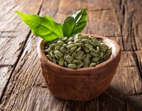 Green coffee beans in wooden bowl Stock Images