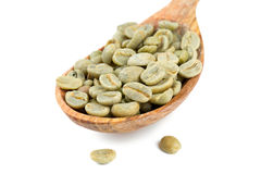 Green coffee beans in a wooden spoon Stock Images