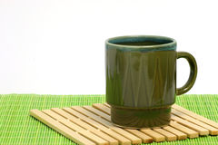 Green coffee cup. On a small placemat Stock Photos