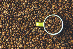 Green coffee cup in coffee beans overhead. Freshly roasted coffee beans and cup Royalty Free Stock Photo