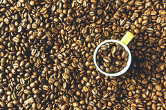 Green coffee cup overhead in coffee beans. Overhead shot of coffee cup in roast coffee beans royalty free stock image