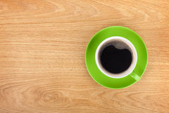 Green coffee cup on wooden table Royalty Free Stock Image