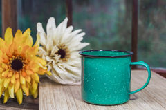 Green coffee mug with flowers. A green mug sits on a table with a paned window in the background and fall mum flowers near by Stock Image