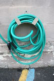Green Coiled Hose Hung On Cement Wall Stock Photo