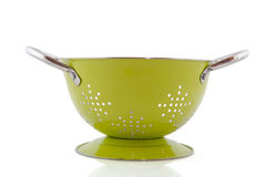 Green colander. As kitchen equipment isolated over white Stock Photos