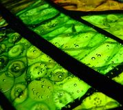 Green cold fusion glass. Green cold fusion stained glass with bubbles and black strokes royalty free stock photo