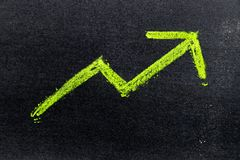 Green color hand drawing chalk in arrow up shape on black board. Background Concept of revenue increase, stock or business growth Royalty Free Stock Image