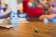 Green color pastel crayon on brown wooden table. Children playing in blurry background. Close up selective focus Stock Image