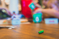 Green color pastel crayon on brown wooden table. Children playing in blurry background. Close up selective focus Royalty Free Stock Photography