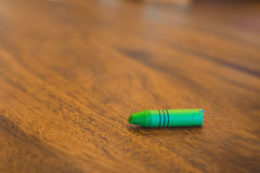 Green color pastel crayon on brown wooden table. Close up selective focus Stock Image