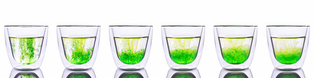 Green color spread in glass of water Royalty Free Stock Photography