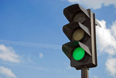 Green color on the traffic light. With a beautiful blue sky in background