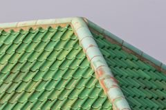 Green colored curved clay roof tiles with ridge corner. Vibrant coloured building roof Royalty Free Stock Photos