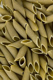 Green colored penne pasta Stock Images