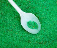 Green colored sand with a spoon as a background Stock Images