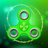 Green colorful spinner on an abstract background with green luminous backdrop.. Abstract background with green luminous backdrop. Modern children`s green toy Stock Photos