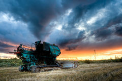 Green combine under sunset Stock Images