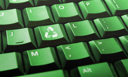 Green computer keyboard with recycle logo. On one of the keys Stock Photography