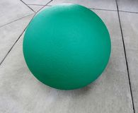 Green concrete sphere on grey concrete background. Green concrete sphere on grey concrete floor Royalty Free Stock Images