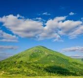 Green conical mountain Stock Photo