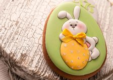 Green cookie with painted easter bunny in yellow bow holding strawberry royalty free stock photos