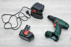 A green cordless drill, a spare battery and a charger on wooden table background. Stock Images