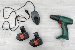 A green cordless drill, a spare battery and a charger on wooden table background. Royalty Free Stock Images