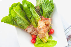 Green cos wrapped in bacon on white dish Stock Images