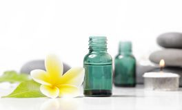 Green cosmetic bottles with zen stones and frangipani flower. Isolated on white stock images