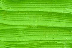 Green cosmetic clay facial mask, cream texture close up, selective focus. Abstract electric lime green background with stripes. Green cosmetic clay facial mask stock image