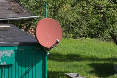 green cottage shack with satellite dish on roof stock photos