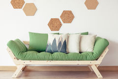 Green couch and cork decor. Cozy interior in natural studio apartment with green couch, wood and cork honeycomb wall decor Royalty Free Stock Image