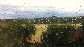 Countryside viewed through a moving train window in a rainy day. Green countryside viewed through a moving train window in a rainy day stock footage
