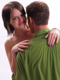 Young Woman Hugging Man. Young adult woman, looking over the shoulder of a man in a green shirt Stock Photos