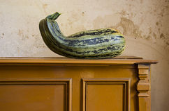 Green courgette on vintage cupboard Stock Photo